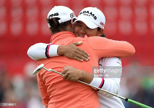Yani Tseng of Taiwan embraces Caroline Masson of Germany on the 18th green following her victory during the final round of the 2011 Ricoh Women's...