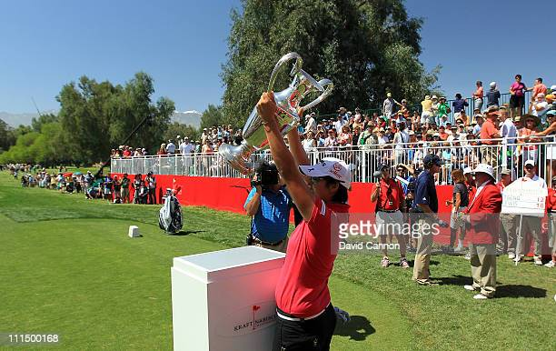 Yani Tseng of Taiwan plays walks onto the 1st tee and raises the trophy she won last year at the start of her final round in the 2011 Kraft Nabisco...