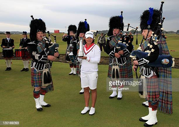 Yani Tseng of Taiwan poses with the trophy and bagpipers following her victory at the end of the final round of the 2011 Ricoh Women's British Open...