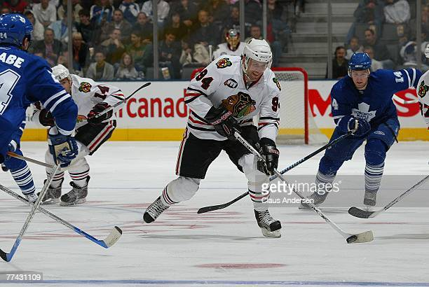 Yanic Perreault of the Chicago Black Hawks skates up ice with the puck followed by Matt Stajan of the Toronto Maple Leafs in a game at the Air Canada...