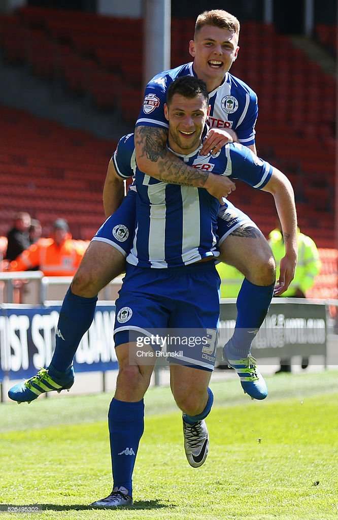 Yanic Wildschut of Wigan Athletic (31) celebrates with team mate Max Power as he scores their third goal during the Sky Bet League One match between Blackpool and Wigan Athletic at Bloomfield Road on April 30, 2016 in Blackpool, England.