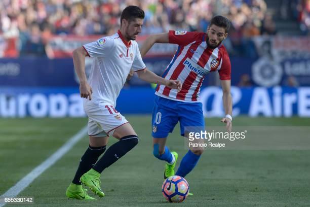 Yanick Carrasco of Atletico de Madrid fights for the ball with Sergio Escudero of Sevilla during the La Liga match between Club Atletico de Madrid...
