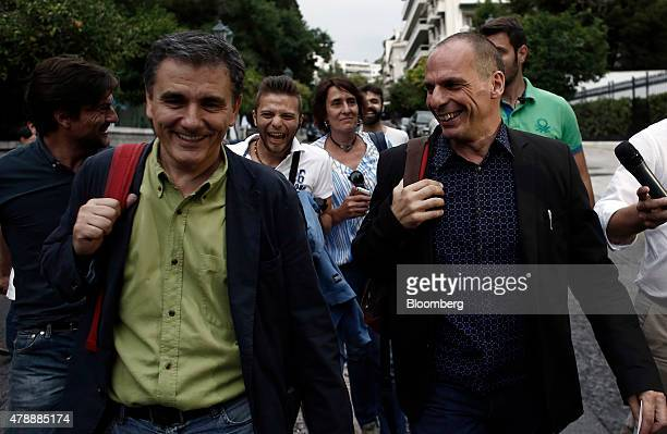 Yanis Varoufakis Greece's finance minister right and Euclid Tsakalotos Greece's deputy foreign minister left react with journalists and pedestrians...