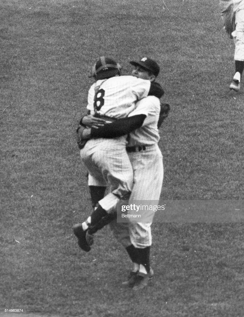 Yankee catcher Yogi Berra jumps up and down as he hugs teammate Don Larsen following Larsen's feat of pitching the first perfect game in World Series...