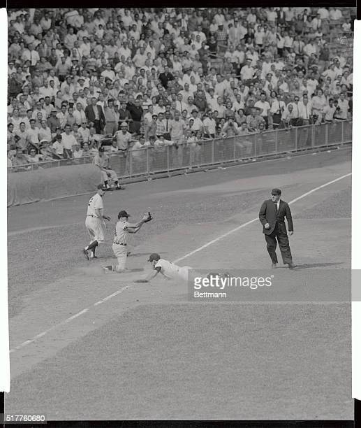 Yankee Yogi Berra hits the dirt as he arrives safely at third base on teammate norm Siebern's single in the ninth inning of New York Chicago game...