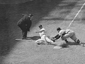 Yankees' catcher Yogi Berra stretches as he tags Detroit's Bill Tuttle from third base on Reno Bertoia's slow roller down the thirdbase line in the...
