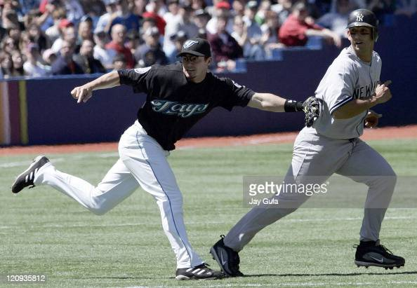 NY Yankees Jorge Posada is tagged out by Toronto SS Russ Adams but the rundown between 2nd and 3rd base allowed Hideki Matsui to score the Yankees...