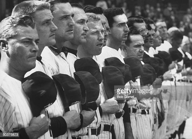 NY Yankees Roger Maris Mickey Mantle Yogi Berra standing in line with other Yankees holding baseball caps over hear during playing of National Anthem...