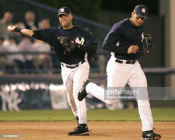 Yankees shortstop Derek Jeter fields a ground ball that was out of reach of third baseman Alex Rodriguez and throws to first in a spring training...
