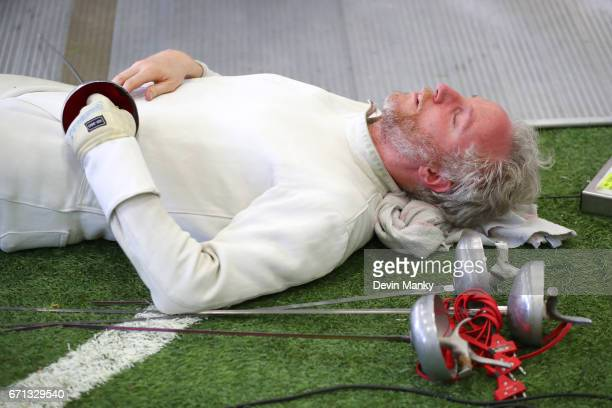 Yann Bernard lays on the ground with his eyes close during a one minute break in action during the Senior Men's Epee event on April 21 2017 at the...