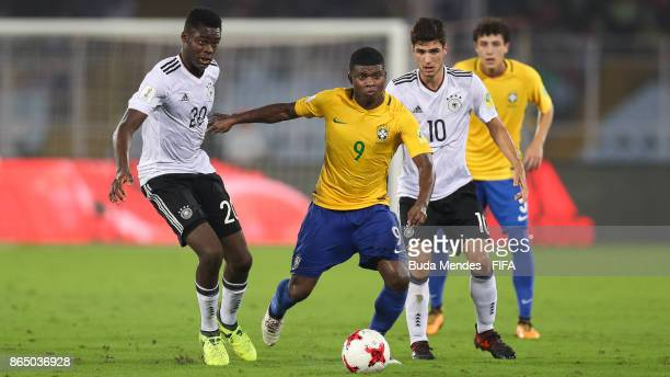 Yann Bisseck and Elias Abouchabaka of Germany battle for the ball with Lincoln of Brazil during the FIFA U17 World Cup India 2017 Quarter Final match...