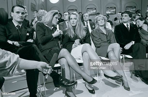 Yann Marine and MarieCaroline Le Pen daughters of French politician JeanMarie Le Pen sit in the audience as their father appears on the television...