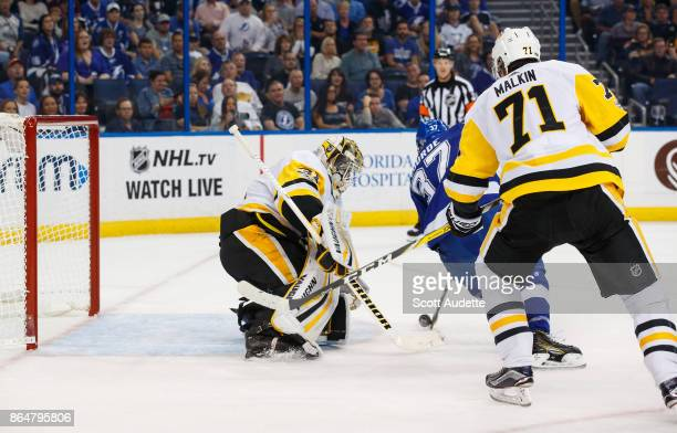 Yanni Gourde of the Tampa Bay Lightning shoots the puck for a goal against goalie Antti Niemi and Evgeni Malkin of the Pittsburgh Penguins during the...
