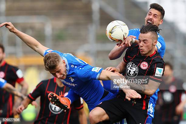 Yanni Regaesel of Frankfurt is challenged by Felix Platte and Sandro Wagner of Darmstadt during the Bundesliga match between SV Darmstadt 98 and...