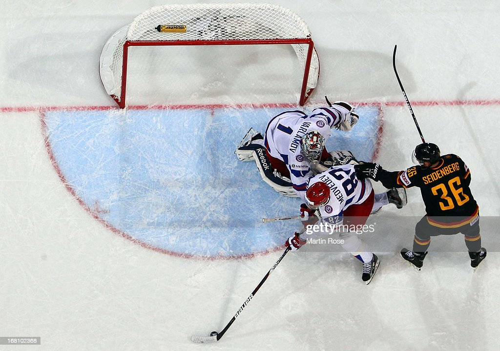 Yannic Seibenberg (R) of Germany and Yevgeni Medvedev (C) of Russia battle for the puck during the IIHF World Championship group H match between Germany and Russia at Hartwall Areena on May 5, 2013 in Helsinki, Finland.