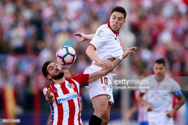 Yannick Carrasco of Atletico de Madrid competes for the ball with Samir Nasri of Sevilla FC during the La Liga match between Club Atletico de Madrid...