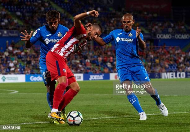 Yannick Carrasco of Atletico de Madrid is tackled by Damian Suarez and Cata Diaz of Getafe during the Pre Season Friendly match between Getafe CF and...
