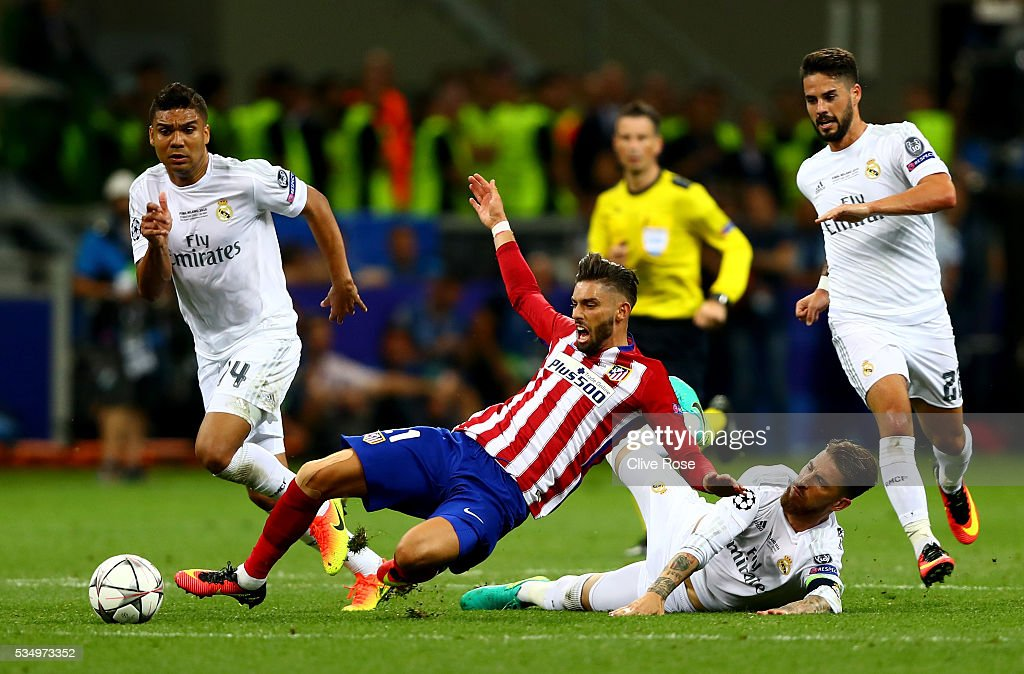 Yannick Carrasco of Atletico Madrid is fouled by Sergio Ramos of Real Madrid during the UEFA Champions League Final match between Real Madrid and Club Atletico de Madrid at Stadio Giuseppe Meazza on May 28, 2016 in Milan, Italy.