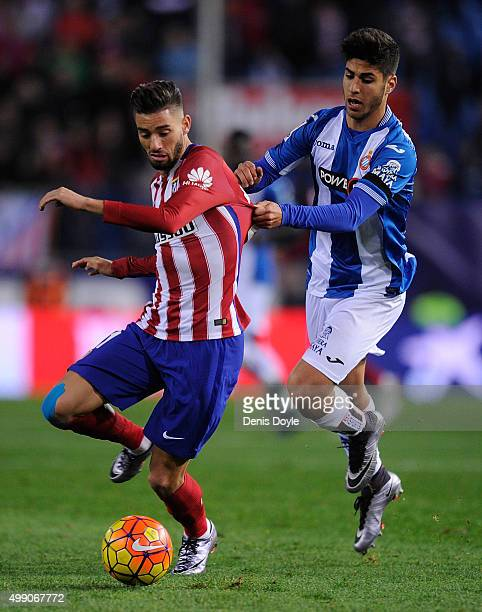 Yannick Carrasco of Club Atletico de Madrid is tackled by Marco Asensio of Real CD Espanyol during the La Liga match between Club Atletico de Madrid...
