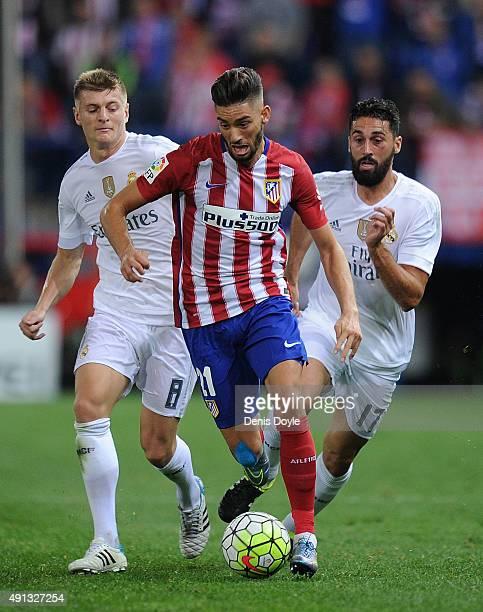 Yannick Carrasco of Club Atletico de Madrid outpaces Toni Kroos and Alvaro Arbeloa of Real Madrid during the La Liga match between Club Atletico de...