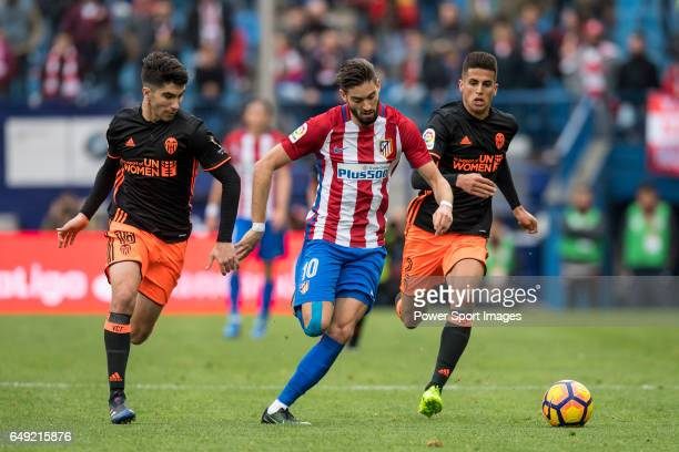 Yannick Ferreira Carrasco of Atletico de Madrid competes for the ball with Carlos Soler of Valencia CF and hist teammate Joao Cancelo during the...