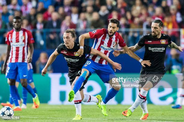 Yannick Ferreira Carrasco of Atletico de Madrid competes for the ball with Julian Baumgartlinger and Roberto Hilbert of Bayer 04 Leverkusen during...