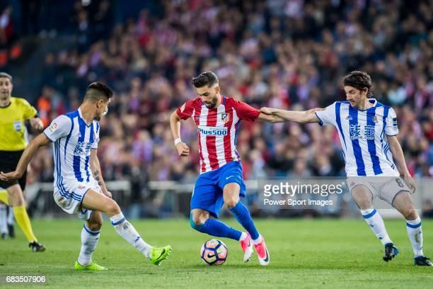 Yannick Ferreira Carrasco of Atletico de Madrid is challenged by Yuri Berchiche Izeta and Esteban Felix Granero Molina of Real Sociedad during their...