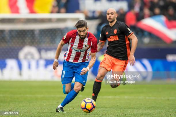 Yannick Ferreira Carrasco of Atletico de Madrid runs with the ball while Simone Zaza of Valencia CF is in pursuit during the match Atletico de Madrid...