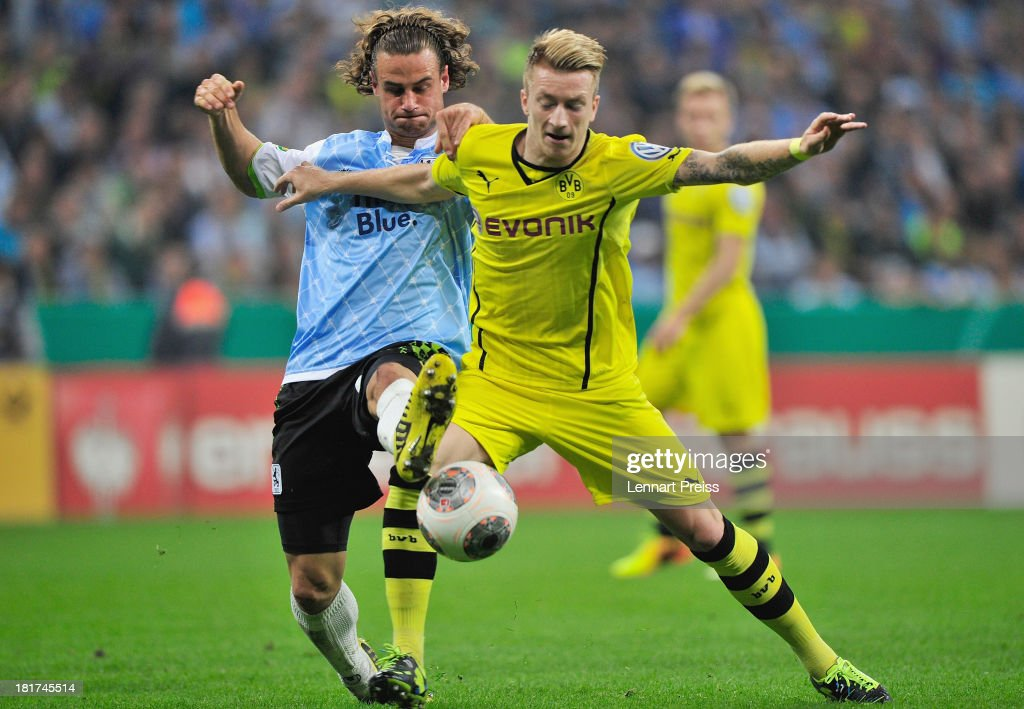 Yannick Stark (L) of Muenchen challenges <a gi-track='captionPersonalityLinkClicked' href=/galleries/search?phrase=Marco+Reus&family=editorial&specificpeople=5445884 ng-click='$event.stopPropagation()'>Marco Reus</a> of Dortmund during the DFB Cup match between TSV 1860 Muenchen and Borussia Dortmund at Allianz Arena on September 24, 2013 in Munich, Germany.