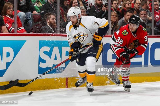Yannick Weber of the Nashville Predators and Ryan Hartman of the Chicago Blackhawks chase the puck in the second period in Game One of the Western...