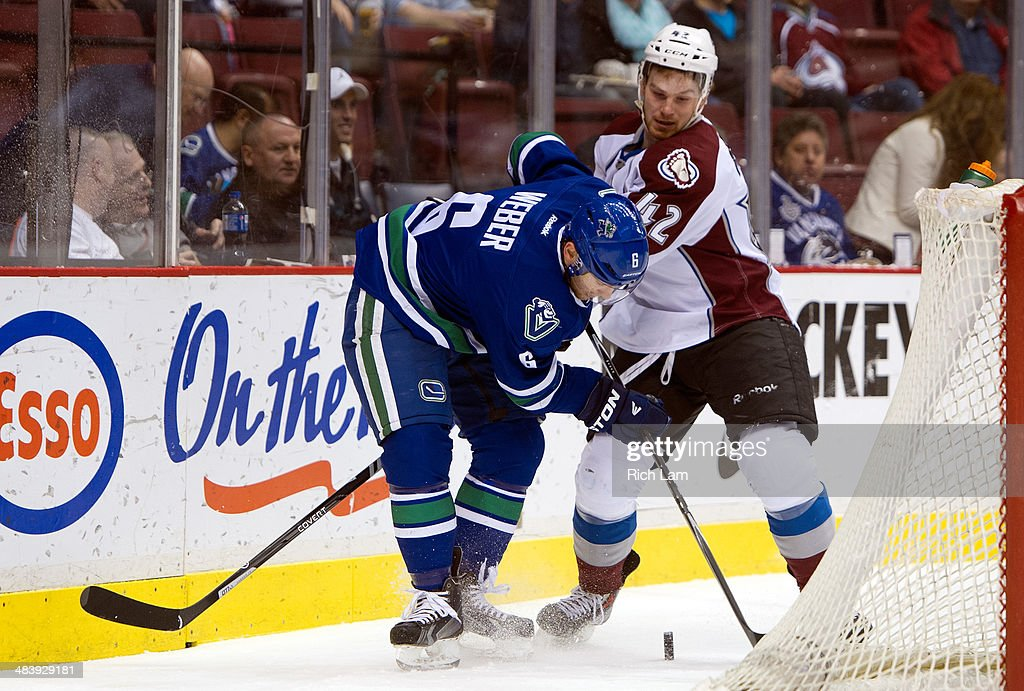 Yannick Weber #6 of the Vancouver Canucks tries to gain control of the puck while being checked by Brad Malone #42 of the Colorado Avalanche while behind the net during the first period in NHL action on April 10, 2014 at Rogers Arena in Vancouver, British Columbia, Canada.