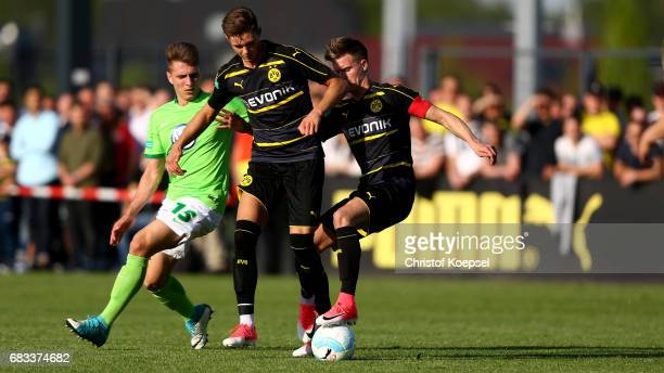 Yannik Moeker of Wolfsburg challenges Alexander Laukart of Dortmund and Dzenis Burnic during the U19 German Championship Semi Final second leg match...