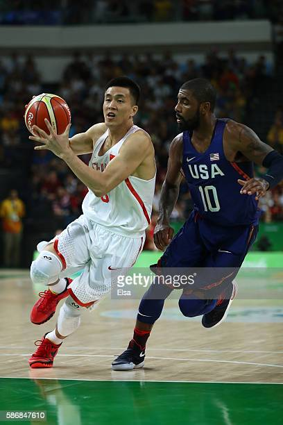 Yanyuhang Ding of China drives the ball around Kyrie Irving of United States in the Men's Preliminary Round Group A match on Day 1 of the Rio 2016...