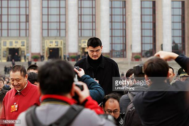Yao Ming NBA basketball star and a delegate to the Chinese People's Political Consultative Conference walks outside the Great Hall of the People...