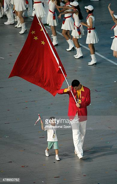 Yao Ming of China carries his country's flag to lead out the delegation accompanied by Lin Hao a 9year old survivivor of the Schenau earthquake...