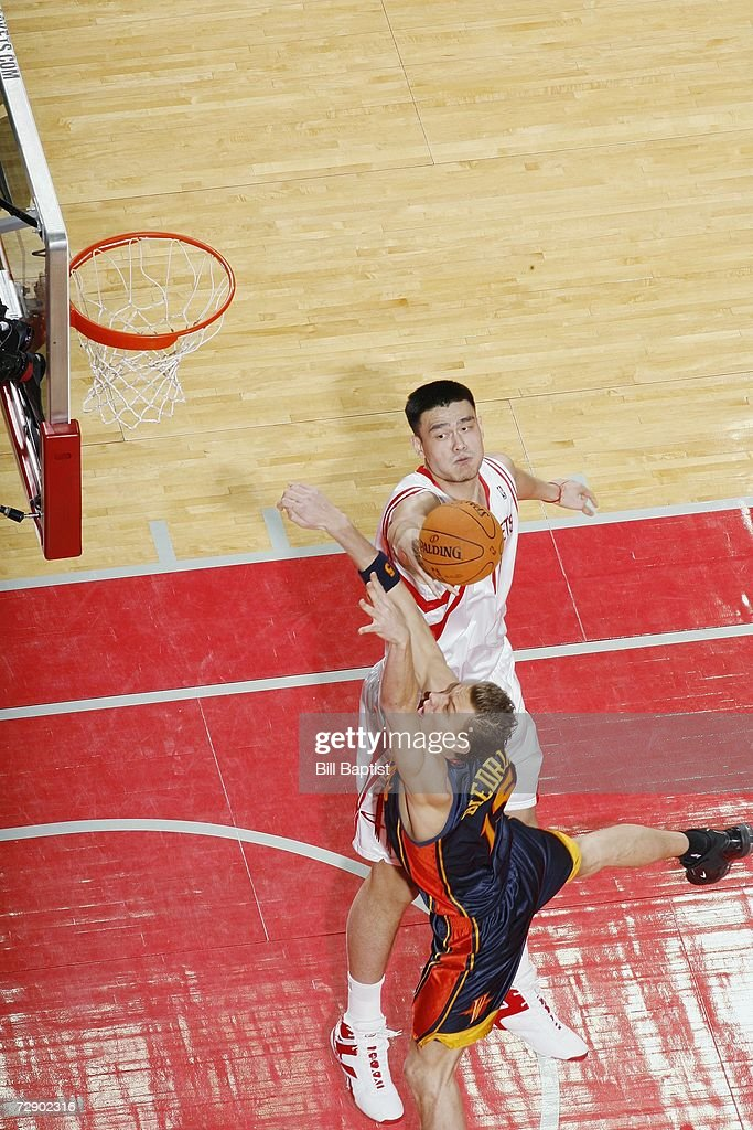 Yao Ming of the Houston Rockets blocks the shot by Andris Biedrins of the Golden State Warriors at the Toyota Center on December 5 2006 in Houston...