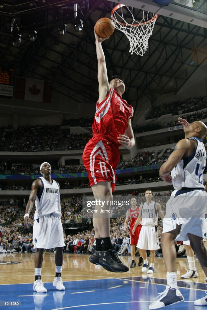 Yao Ming #11 of the Houston Rockets dunks over Scott Williams #42 of the Dallas Mavericks during the game at the American Airlines Arena on February 21, 2004 in Dallas, Texas. The Mavericks won 97-88.