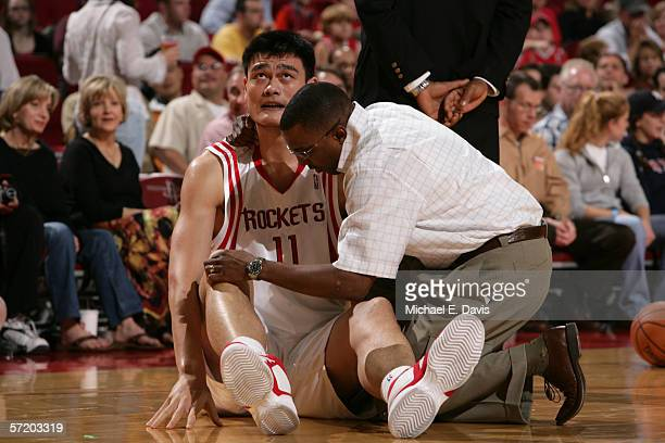 Yao Ming of the Houston Rockets has his knee examined by Rockets trainer Keith Jones during the game against the San Antonio Spurs on March 18 2006...