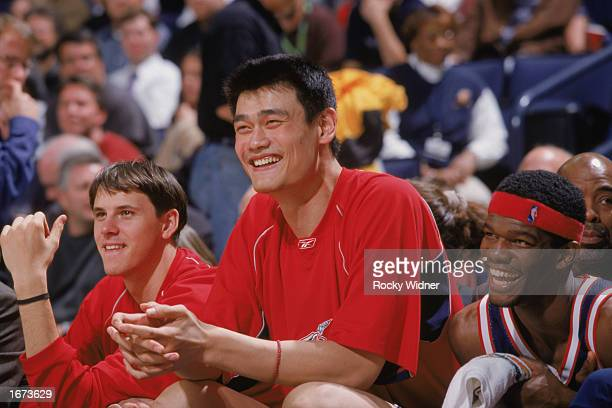 Yao Ming of the Houston Rockets smiles with teammates on the bench during the NBA game against the Golden State Warriors at The Arena in Oakland on...