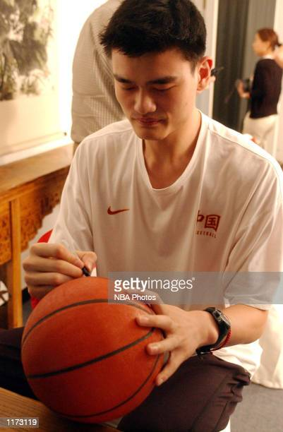 Yao Ming signs an autograph after being chosen first overall in the 2002 NBA Draft on June25 2002 by the Houston Rockets Shanghai China NOTE TO USER...