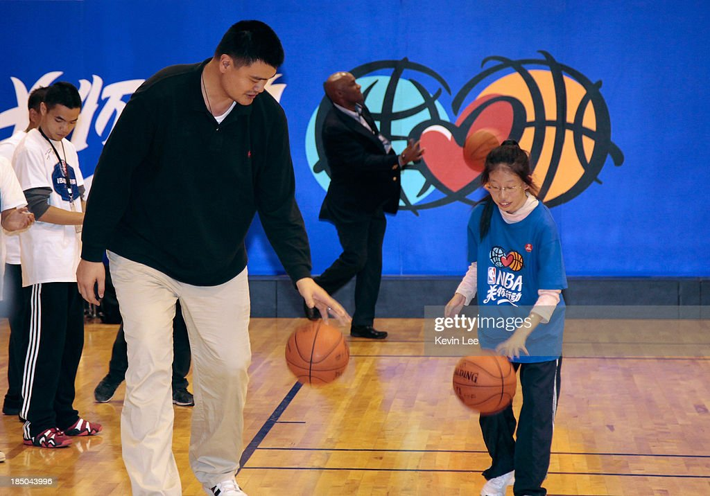 <a gi-track='captionPersonalityLinkClicked' href=/galleries/search?phrase=Yao+Ming&family=editorial&specificpeople=201476 ng-click='$event.stopPropagation()'>Yao Ming</a> teaches a young girl basketball at NBA Fan Appreciation Day on October 17, 2013 in Shanghai, China.