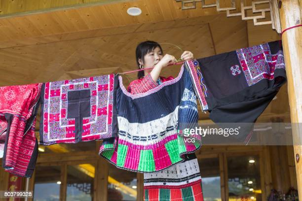 Yao minority girl hangs her beloved clothes dresses and exquisite accessories on bamboo poles and window frames during the Shanyi Festival on June 29...