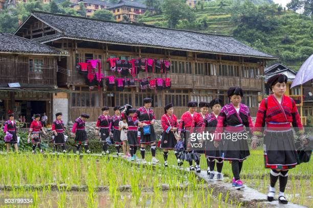 Yao minority girls hang their beloved clothes dresses and exquisite accessories on bamboo poles and window frames during the Shanyi Festival on June...