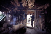 Yao tribesman with his hunting gun stands outside the smoky interior of his hut in the village of Ban Hway Long a day's walk from Muang Sing in...
