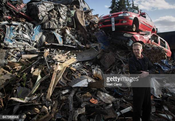 Yard owner Ped Rossiter poses for a photograph in front of a pile of scrap metal and scrap cars waiting to be processed at Pylle Motor Spares and...