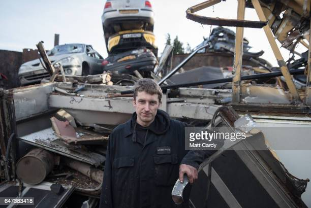 Yard owner's son Jamie Rossiter poses for a photograph in front of a pile of scrap metal and scrap cars waiting to be processed at Pylle Motor Spares...