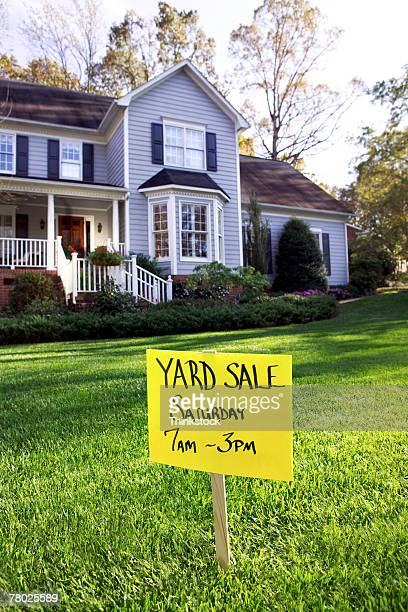 A ?Yard Sale' sign posted in front of a suburban home