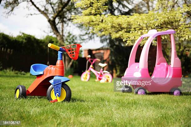 A yard with three children's toys in it