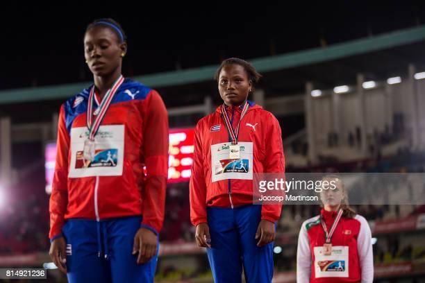 Yaritza de la C Martinez Amanda Almendariz of Cuba and Katsiaryna Valadkevich of Belarus pose during the girls hammer throw medal ceremony during day...