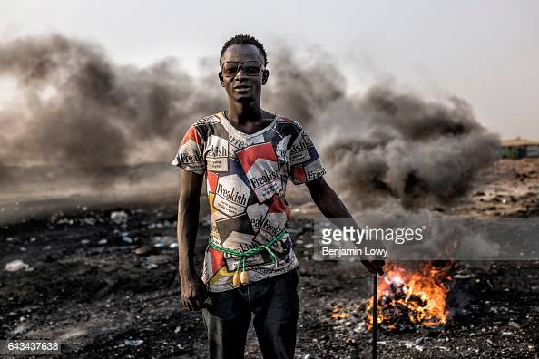 Yaro the selfstyled leader of a band of migrant teens poses in front of the copper burning grounds in the Agbogbloshie dump site His pants are held...